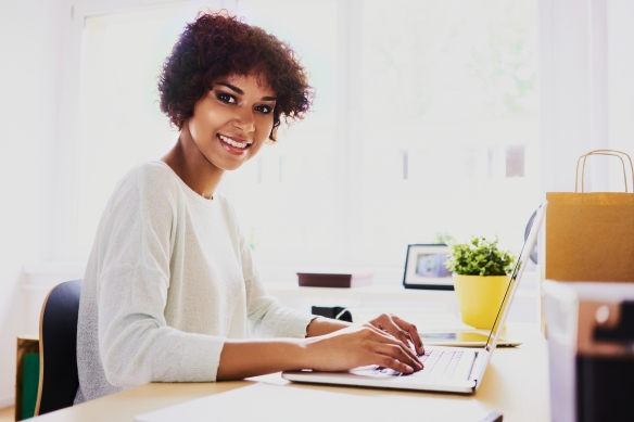 Happy african woman working from home on laptop