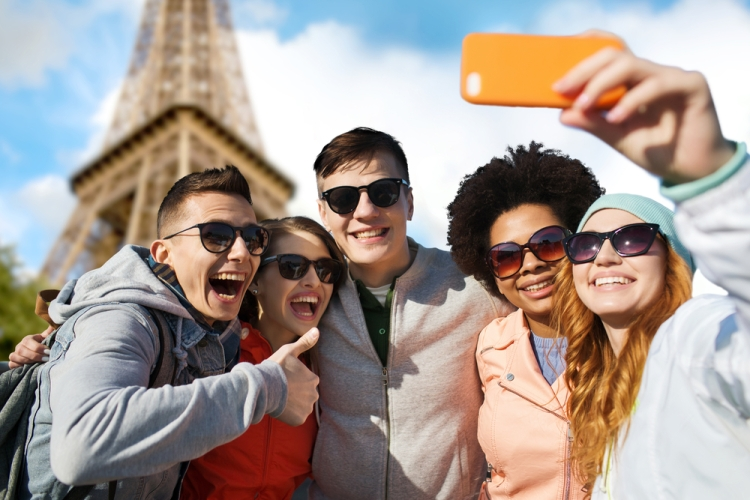 smiling friends taking selfie with smartphone
